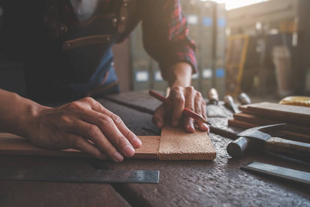 Carpenter working with equipment on wooden table in carpentry shop. woman works in a carpentry shop. stock photo