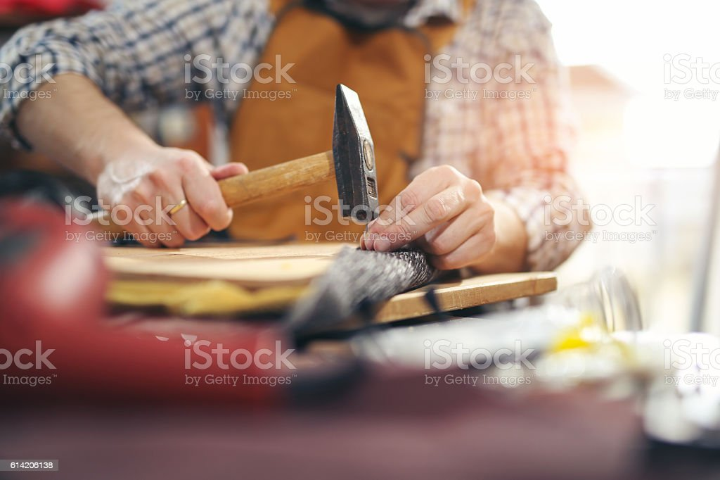 Carpenter working with hammer in his workshop, close up stock photo