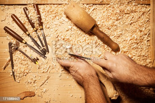 Carpenters' hands, working on a piece of wood. Professional tools on a wooden table in the workshop. Surface covered with sawdust.
