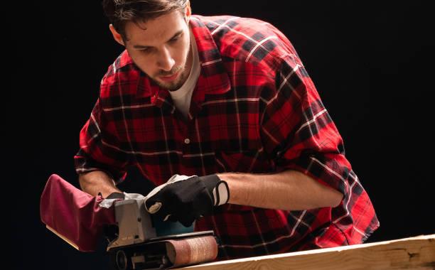 Schreiner arbeitet mit Bandschleifer in der Schreinerei – Foto