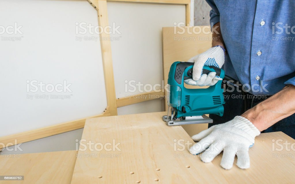 Carpenter Works with Jigsaw stock photo