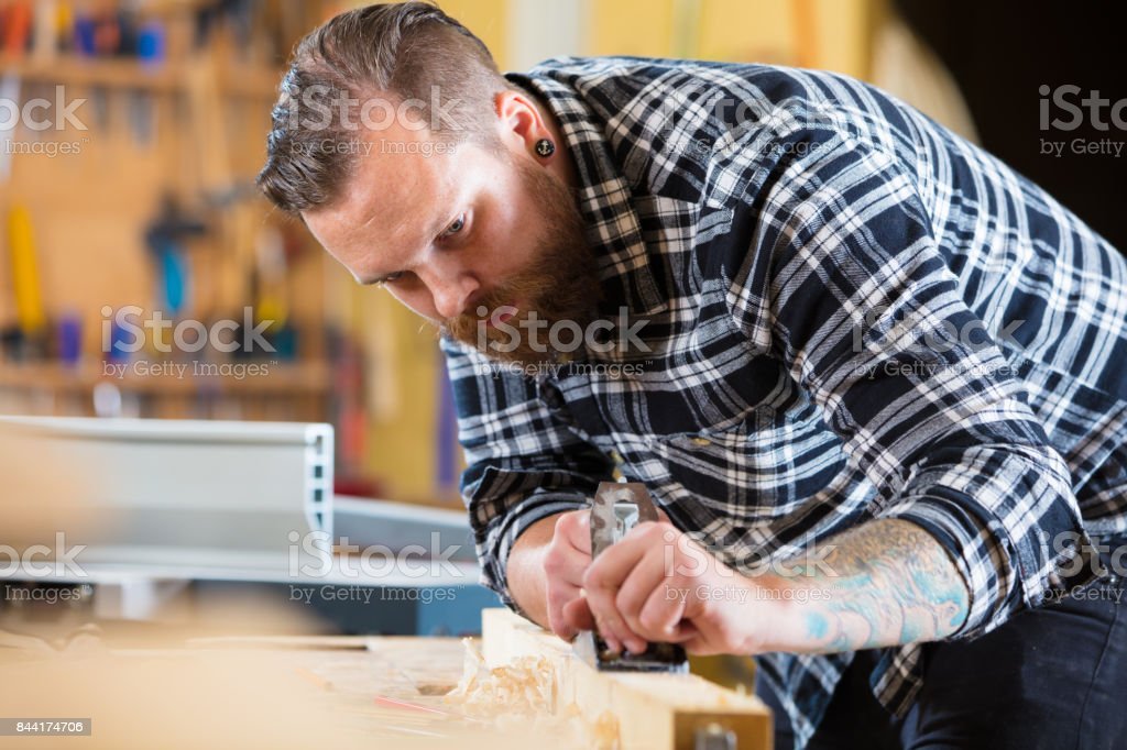 Carpenter works with plane on wood plank in workshop stock photo