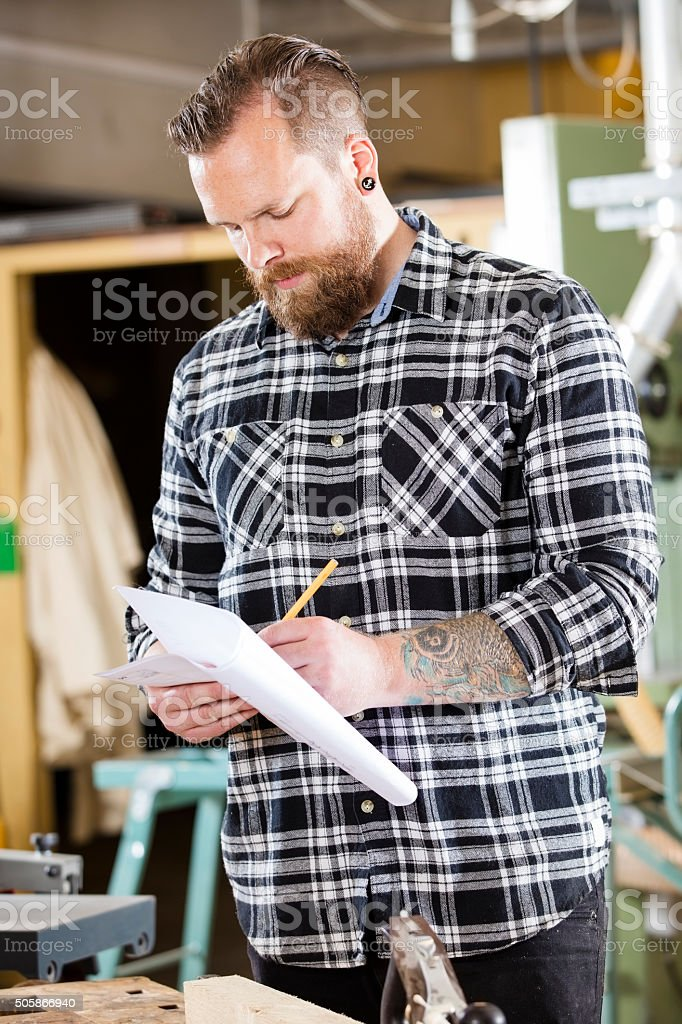 Carpenter writing at drawings in the workshop stock photo