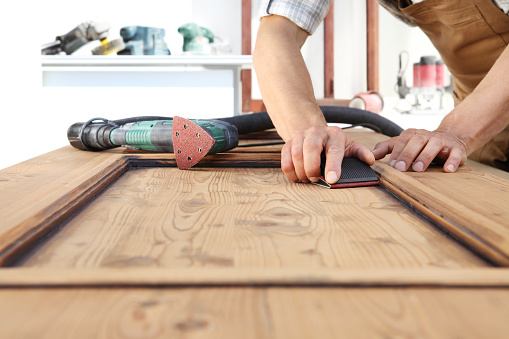 1015564946 istock photo carpenterr hands work the wood with sandpaper and sander 1029899894