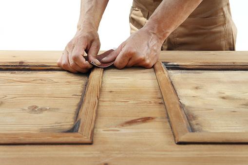1015564946 istock photo carpenterr hands work the wood with sandpaper 1029899922