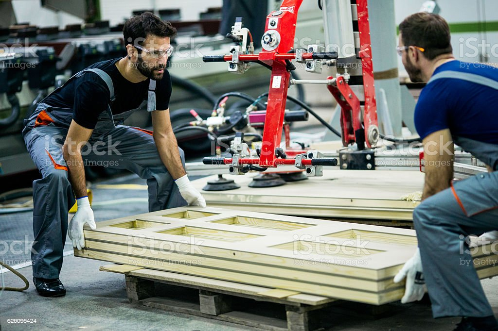 Carpenters carrying wood plank stock photo