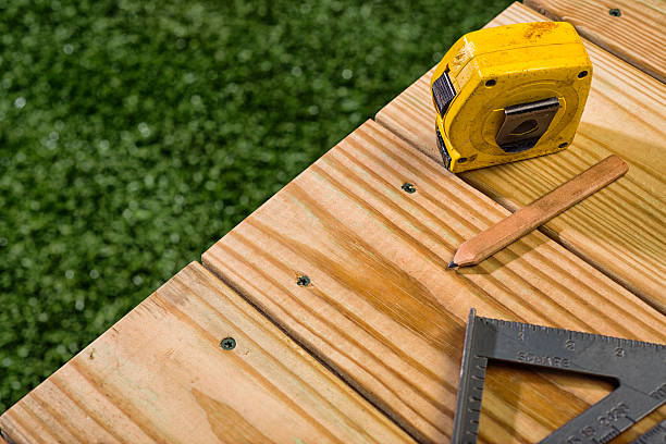 Carpenter's Pencil, square and tape sitting on a wood deck stock photo
