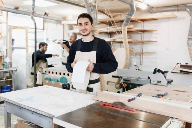 Porträt des Tischlers in Arbeitskleidung vor Werkbank. Porträt von lächelnden Mann bei der Arbeit in der Tischlerei. Startup-Unternehmen, junge Spezialisten. Handwerker macht eigenen erfolgreichen Kleinunternehmen. – Foto