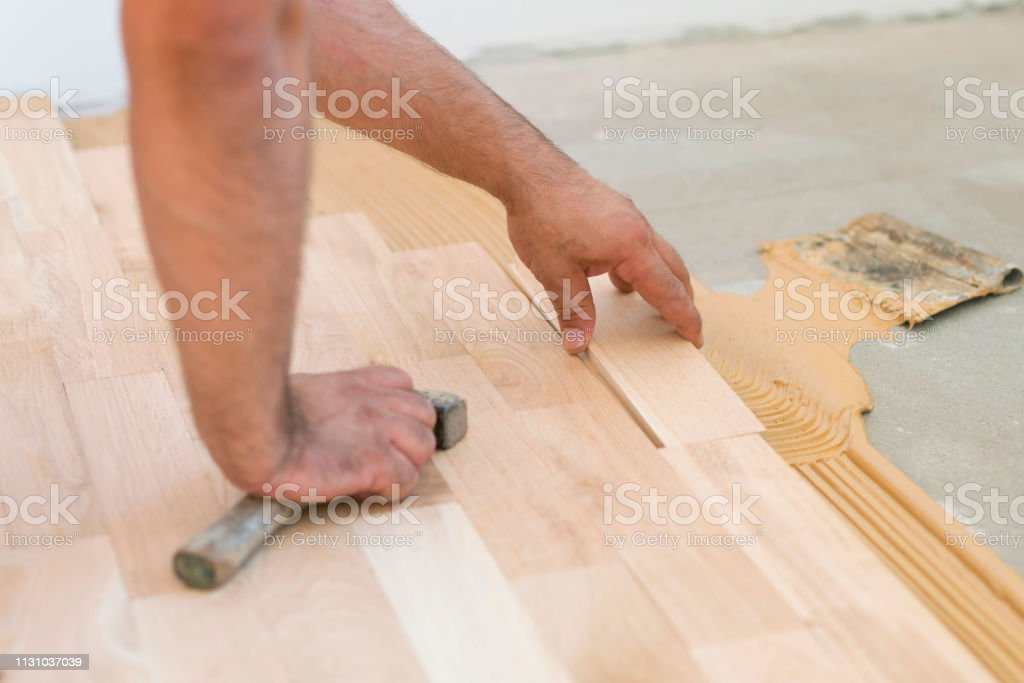 Carpenter and a small business owner laying down parquet planks and...