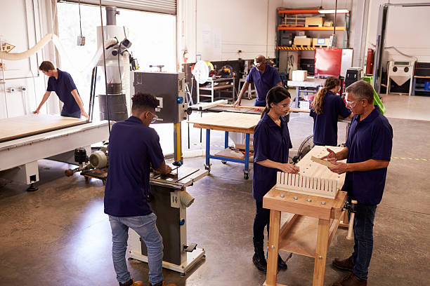 Carpenters Working On Machines In Busy Woodworking Workshop stock photo