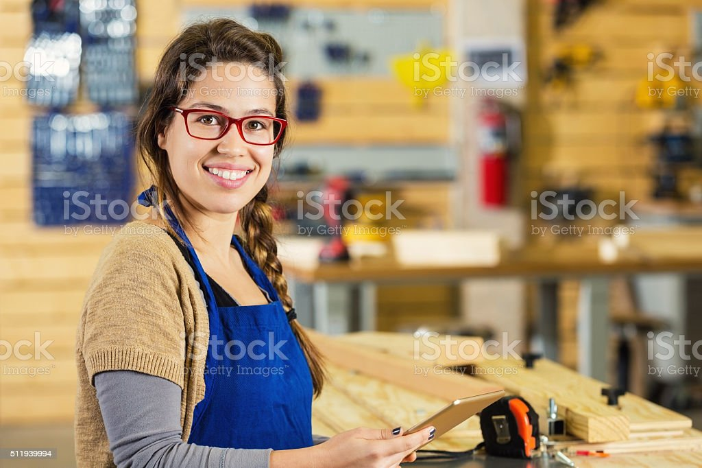 Carpentry apprentice using digital tablet while building furniture stock photo