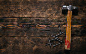 Hammer and nails on a wooden board background with copy space. Woodwork. Carpentry.