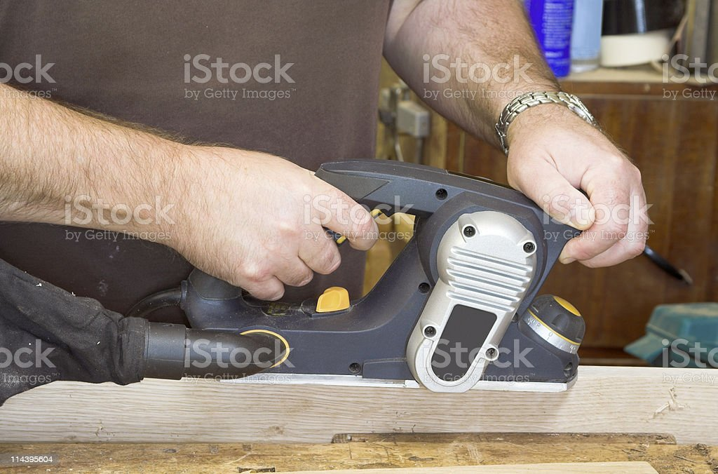 Carpentry - Using A Power Planer royalty-free stock photo