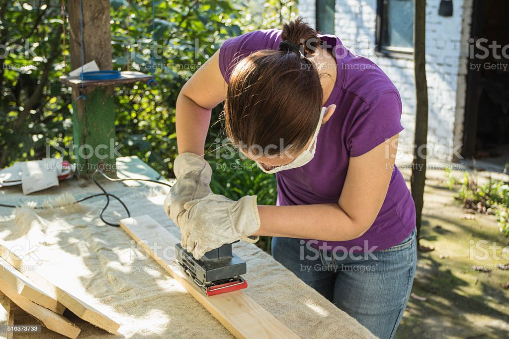 DIY carpentry - woman sanding planks stock photo