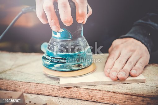 Carpentry. Wood sanding. Orbital sander for woodworking. Carpenter grinds a wooden product with a grinder.
