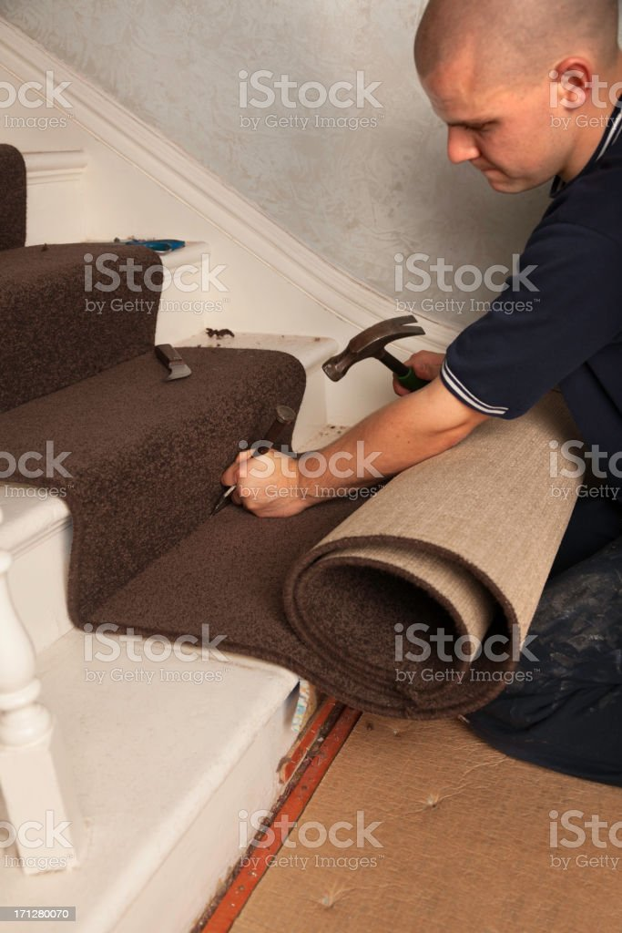 Carpet Fitter using tucking tool on stairs stock photo