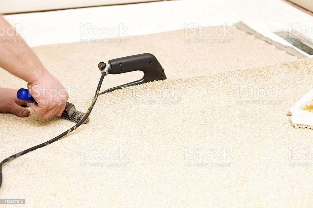 Carpet Installer Joining Two Pieces with Iron and Roller stock photo