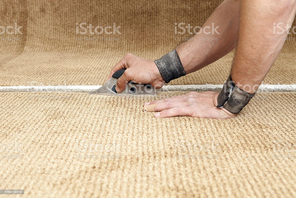 Carpet Installer Using Cushion Back Cutter stock photo