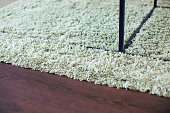 Close-up on beige shag rug, black metal table legs and brown laminate floor.