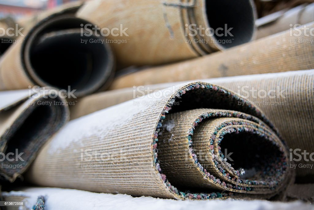Rolled up old dirty carpets, trowed out on the street and covered by...