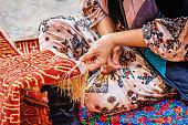 Detail of a female uzbek carpet weaver weaving a typical oriental uzbek silk carpet in Itchan Kala Old Town, Xiva - Khiva - Chiva, Xorazm Region, Uzbekistan, Central Asia
