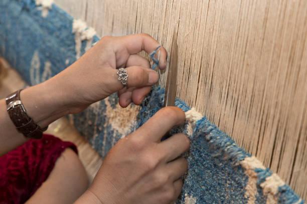 Carpet weaving in Uzbekistan. Woman hands weaving carpet, Uzbekistan. armenian culture stock pictures, royalty-free photos & images