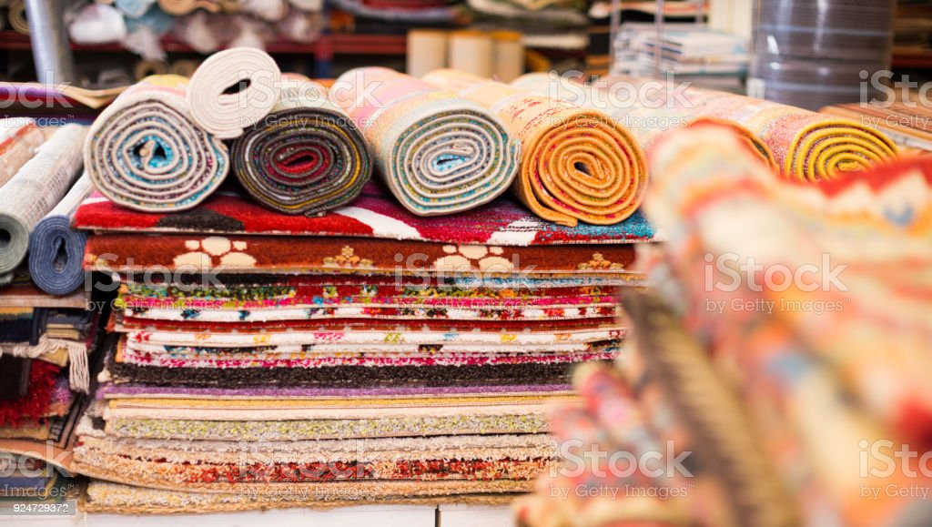 Carpets of different colours in stack at carpet store, no people