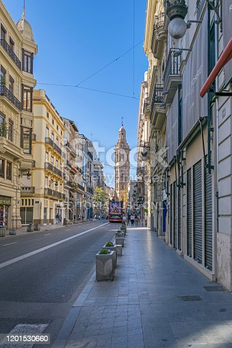 Valencia, Spain - November 3, 2019: Carrer de la Pau with the eighteenth century Baroque belfry of the Santa Catalina church standing out from the rest of the building