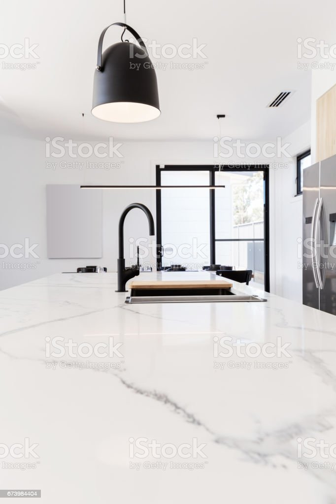 Carrera marble benchtop with black goose neck kitchen tap stock photo