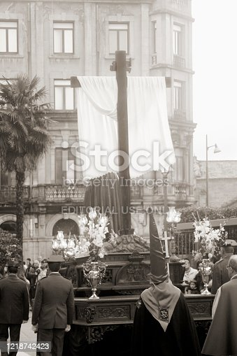 Lugo, Spain - April 19, 2019: Holy Week parade  Lugo city, Galicia, Spain.  Parade float with a  crucifixion scene, wooden cross with a white rag. Flower arrangements, old lamps. Retro styled, black and white view.