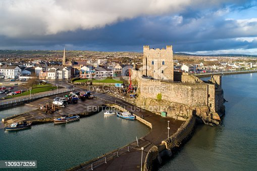 Carrickfergus, Northern Ireland, UK - February 1, 2020:.Medieval Norman Castle, harbor with boat ramp and wave breaker in Carrickfergus near Belfast. Aerial view in sunset light in winter. Town and stormy clouds in the background
