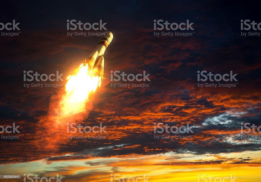Carrier Rocket Takes Off On A Background Of Red Clouds stock photo