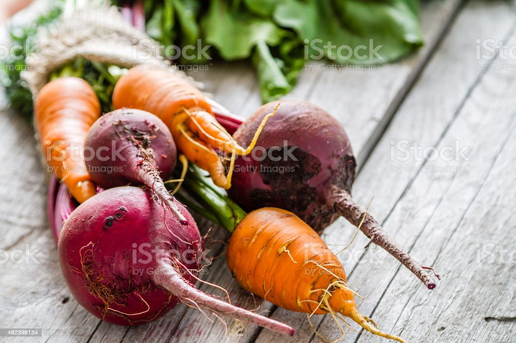 Carrot and beet on rustic background stock photo
