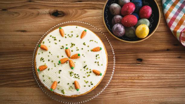 Karottenkuchen und bunte Eier auf hölzernem Ostertisch – Foto