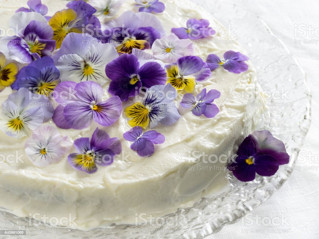 Carrot cake, decorated with edible flowers pansies stock photo