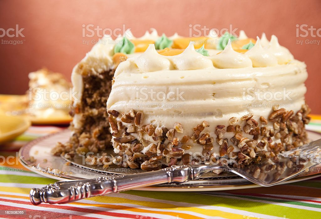 Carrot cake with slices missing and silver server on plate. royalty-free stock photo
