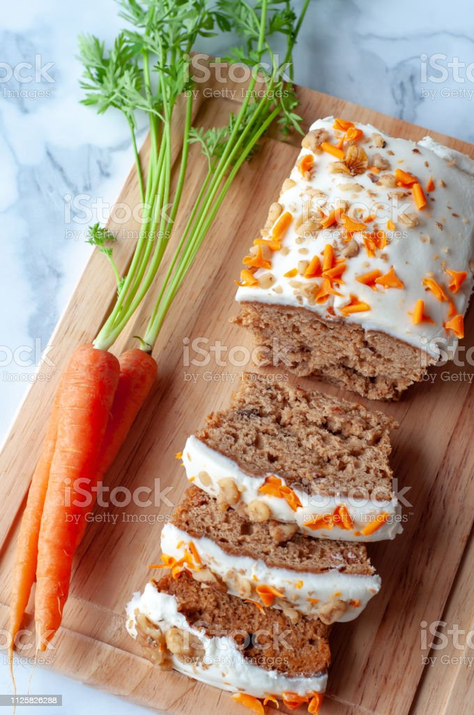 Carrot cake loaf with whole carrots arranged on wooden cutting board