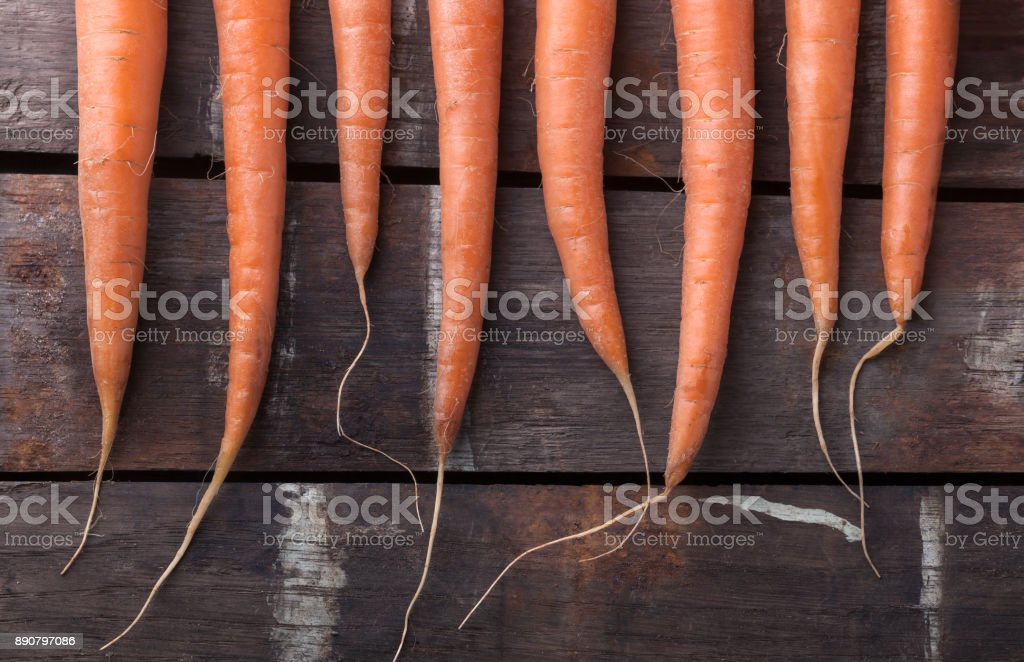 Carrot closeup group lined up on old brown wooden table stock photo