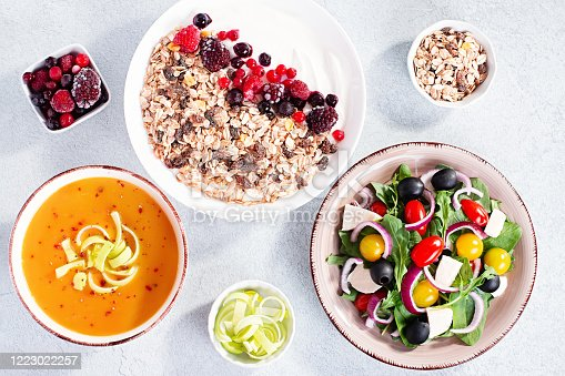 Carrot cream soup, Greek salad, muesli bowl with yogurt on concrete table top with copy space. Assortment of dishes for diet, suitable for volumetrics diet and other nutrition strategies