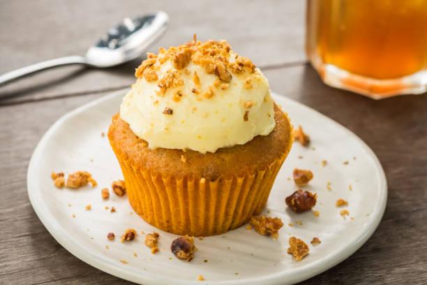 carrot cupcake with cream cheese and hazelnuts - vanille muffins stock-fotos und bilder