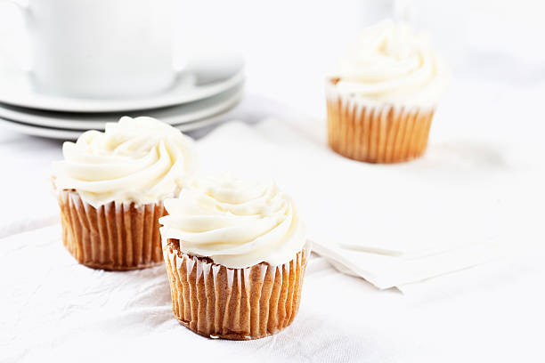 carrot cupecakes with vanilla icing carrot cupecakes with vanilla icing on white table cloth, white cups in background buttercream stock pictures, royalty-free photos & images