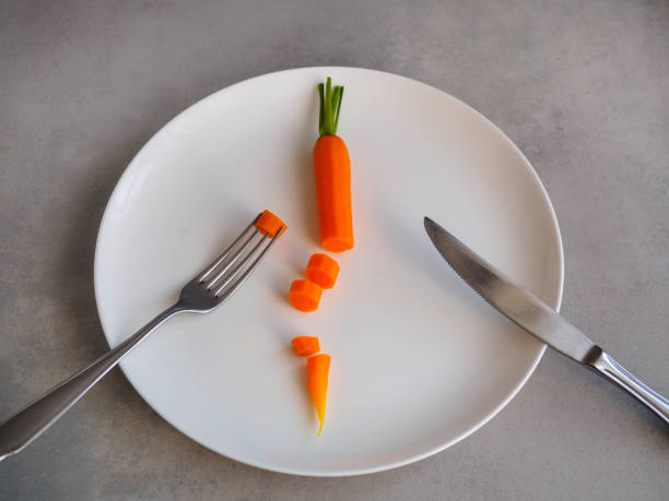 Carrot cut on a white plate, esmal Speisen, Gemüse, Essbesteck, Geschirr, Tisch, Diät, Fasten, Magersucht lent stock pictures, royalty-free photos & images