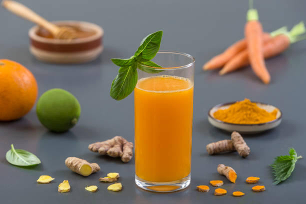 Carrot ginger immune boosting, anti inflammatory smoothie with turmeric and honey. Detox morning juice drink, stock photo