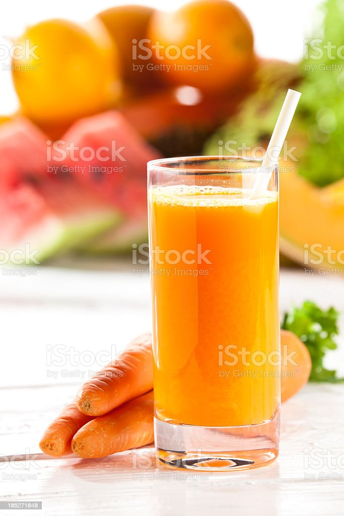 Carrot juice glass on white garden table royalty-free stock photo