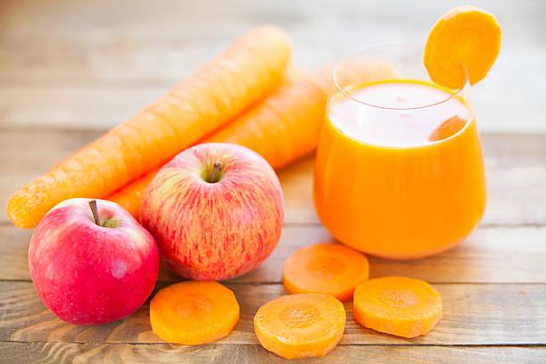 carrot juice in glass on  table - meyve ve sebze suyu soğuk i̇çecek stok fotoğraflar ve resimler