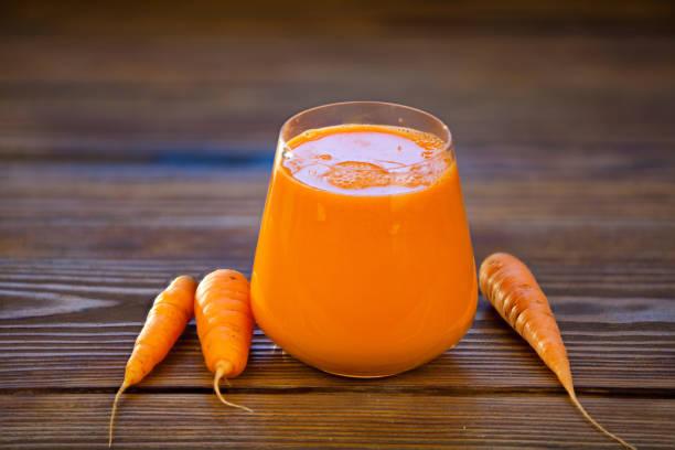 zumo de zanahoria en vidrio en la tabla - vitamina a fotografías e imágenes de stock