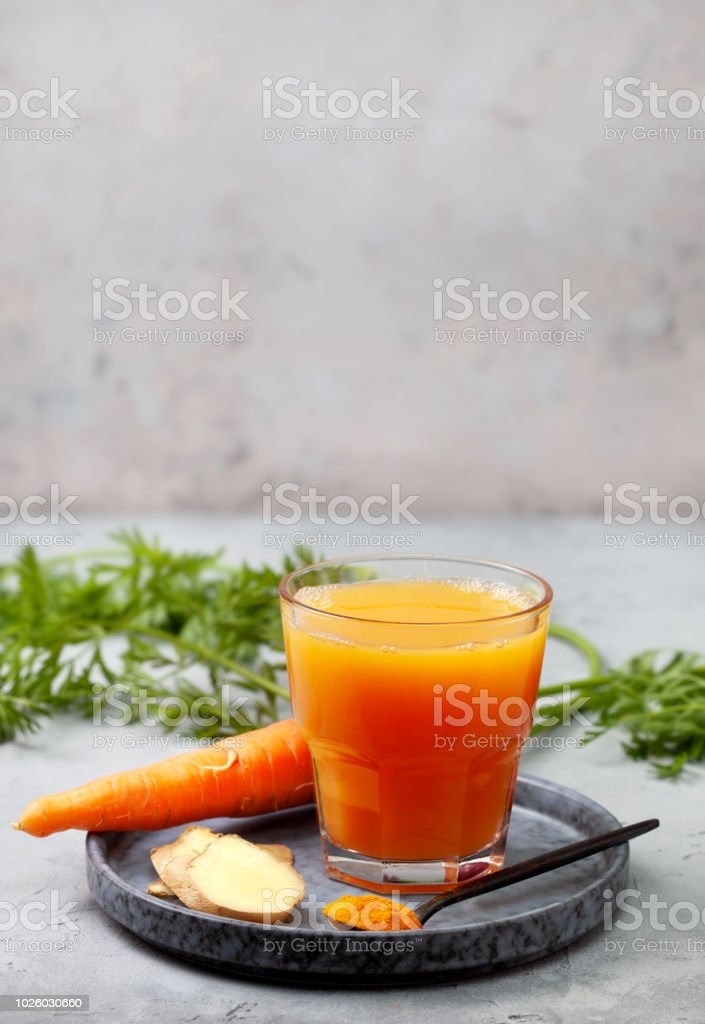 detox drink. carrot, ginger, turmeric drink in a glass on a gray...