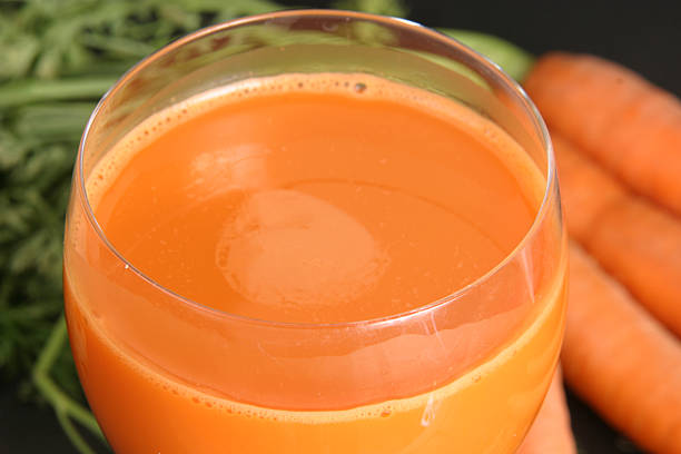 Carrot juice with carrots in the background stock photo