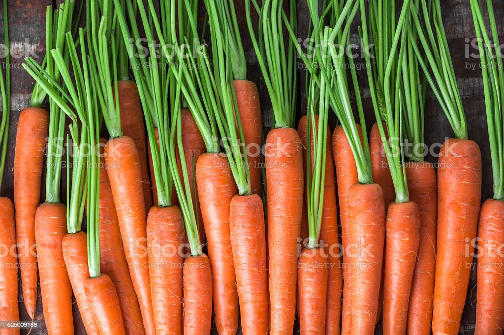 Carrot overhead group lined up on old brown wooden table stock photo