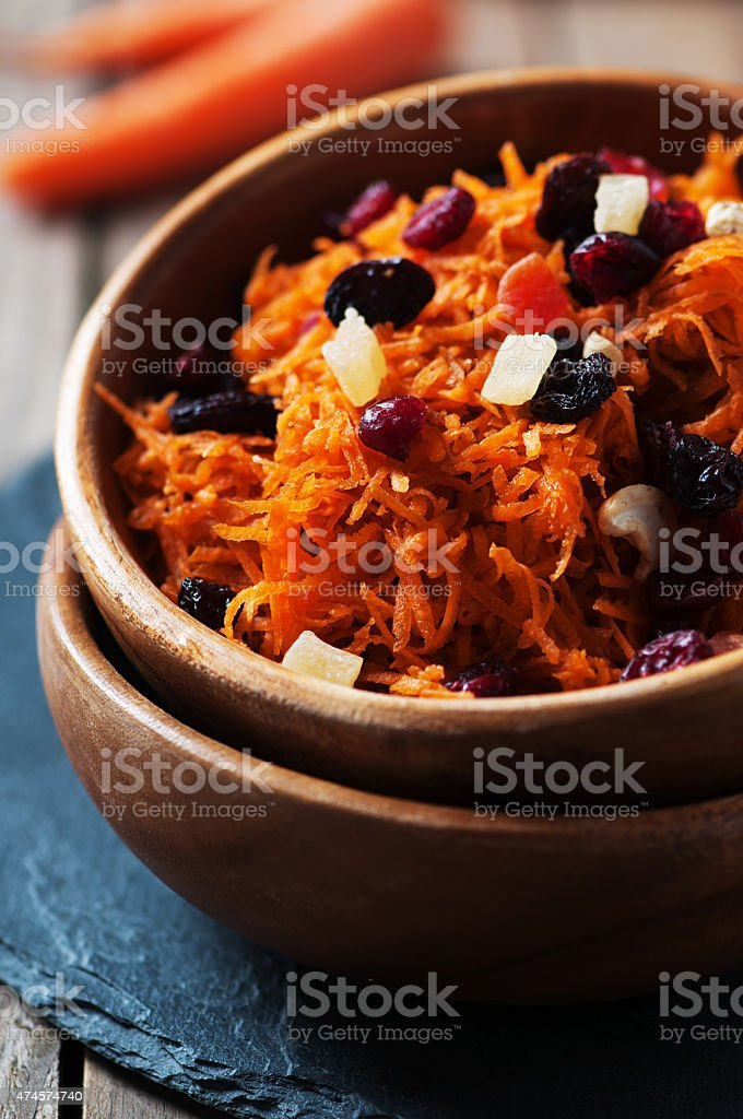 Carrot salad with raisins on the wooden table stock photo